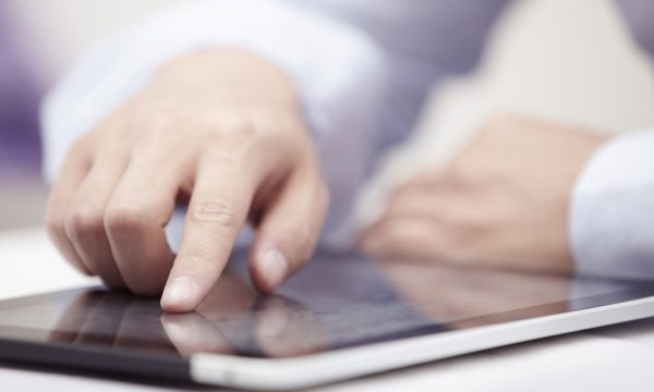 Hands of businessman using tablet PC at office